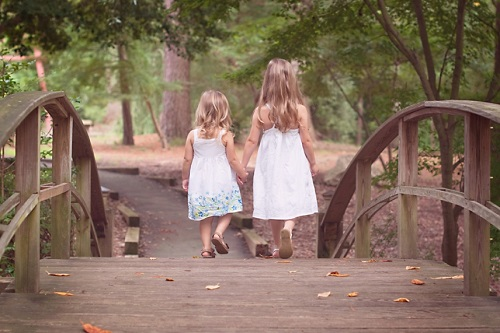 Two-sisters-holding-hands-across-a-bridge-in-the-woods-1pp w856 h571 1
